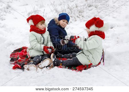 Sisters Twins And An Elder Brother Are Sitting On A Warm Plaid And Pouring Hot Tea From A Thermos Du