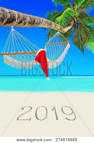 Red Christmas Santa Claus Hat On Wooden Mesh Hammock Under Coconut Palm Tree At Paradise Tropical Be