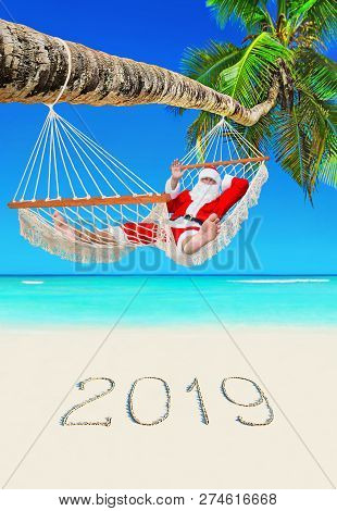 Santa Claus Relax In Hammock At Tropical Palm Beach With Handwritten Caption Of New Year 2019 On Whi