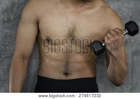 Muscular Bodybuilder Guy Doing Exercises With Dumbbells In Gym On Cement Background.