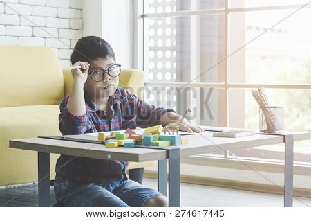 Boy Dreaming To Drawing With Pencils In Colorful Jar On The Table.