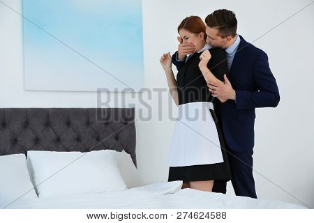 Man Molesting Chambermaid In Bedroom. Sexual Harassment At Work