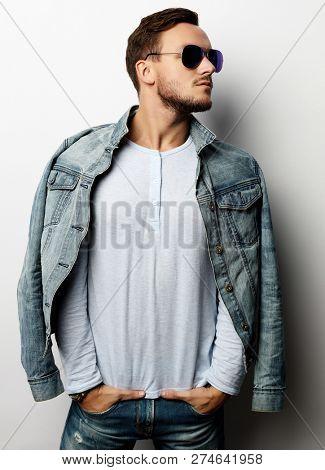 Elegant young handsome manin smart casual wear and sunglasses. Studio fashion portrait.