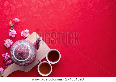 Teapot And Cup Of Tea With Copy Space For Text On Red Texture Background, Chinese New Year Backgroun