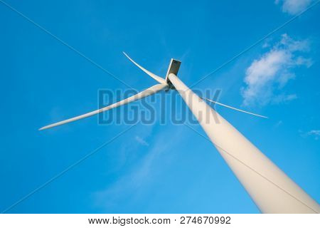 View Up, Bottom View Of Wind Turbine, Windmill Isolated On Blue Sky Background. Royalty High-quality