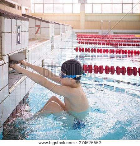 Cute Little Kid Boy Is Ready For Swimming Competition  In The Sport Swimming Pool. Child Ready To Ju