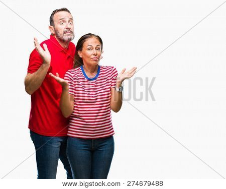 Middle age hispanic couple in love over isolated background clueless and confused expression with arms and hands raised. Doubt concept.