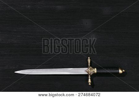 Dagger Knife Isolated On The Black Wooden Background With Copy Space.