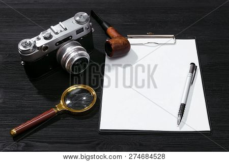 Blank Page, Pen, Film Photo Camera, Magnifying Glass And Smoking Pipe On A Black Detective Agent Tab
