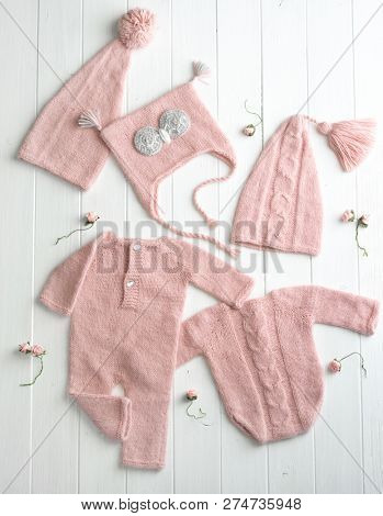 Pink small knitted clothes for babies composed on the white table