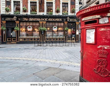 London, Uk - 4 December 2018: An Old Red Post Box Outside A Traditional English Pub, The Sherlock Ho