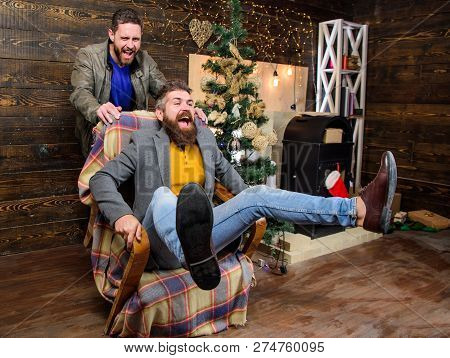 Break Into New Year With Fun. Best Friend Having Fun On Christmas Eve. Man Push Armchair With Friend