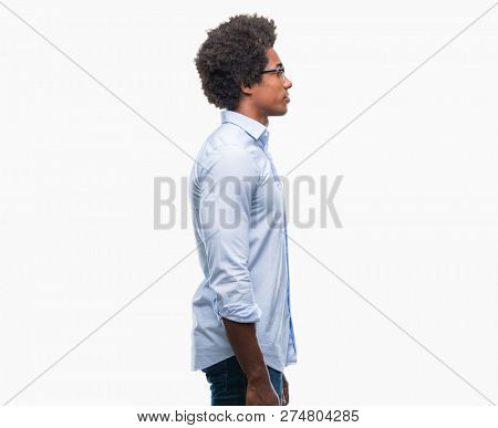 Afro american business man wearing glasses over isolated background looking to side, relax profile pose with natural face with confident smile.