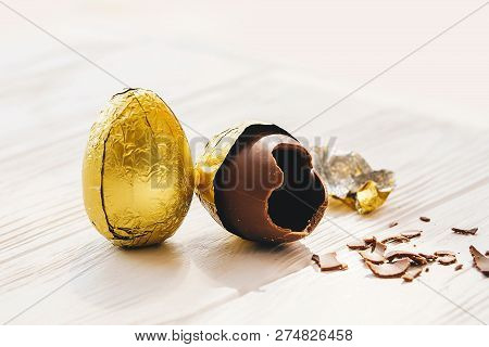 Stylish Easter Chocolate Egg In Golden Foil And Broken Chocolate Egg On White Wooden Background . Mo