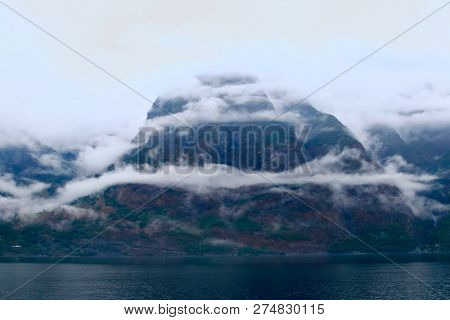 Fog And Mountains Landscape All Along Te Shores Of The Naeroyfjord, North Of Gudvangen Village, Norw