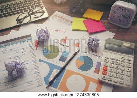 Business Computer Office Desk With Desktop Laptop,crumpled Paper,glasses,calculator,clock And Annual