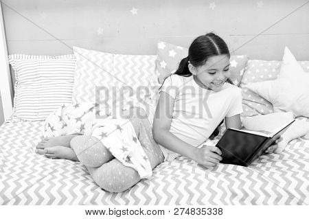 Fascinating Story. Girl Child Lay Bed With Pillows Read Book. Kid Prepare To Go To Bed. Time For Eve