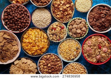 Assortment of various kinds cereals placed in ceramic bowls with cornflakes, granola, cereals and oatmeal. Flat lay, top view on blue rusty table with copy space in the middle