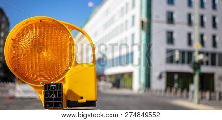 Road construction concept. Orange reflector warning light protects the drivers. Blur city background, space, banner.