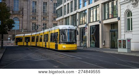 Public transportation concept. Yellow electric tram travels at Berlin's town, Germany. City background, banner.