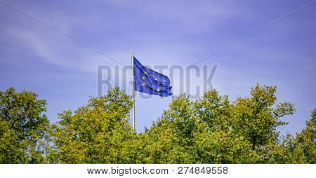 EU flag on pole. Waving flag of European Union over green trees. Blue sky background.