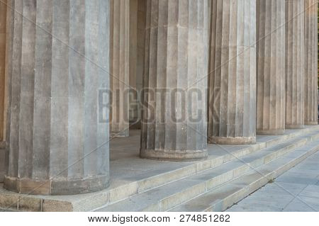 Ancient pillars and steps of grey marble, ionic rhythm. Historic heritage, close up view with details.
