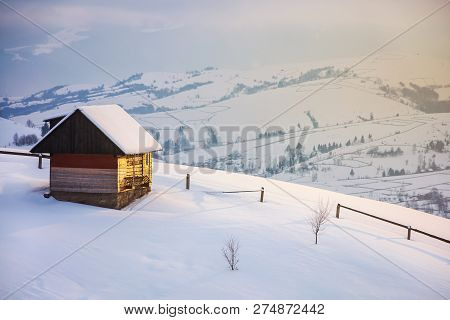 Outskirts Of The Village On The Hill. Woodshed Behind The Wooden Fence On A Snowy Slope. Peaks Of Th