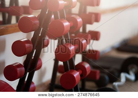 Two Vertical Rows Of Red Metal Dumbbells On Rack In The Gym Sport Club. Weight Training Equipment Se