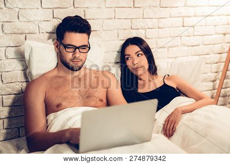 Young Couple In Bed, Man Working Laptop Bored Wife. Businessman Working On Computer In Bed While Wif