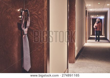 Tie Hanging On A Hotel Closed Door Handle, Do Not Disturb Informal Sign, Retro Color Toning Applied,