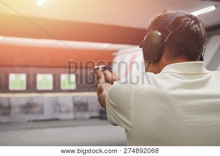 Man Shoots Pistol In Noise Protection Headphones. Shooting Range Gun.
