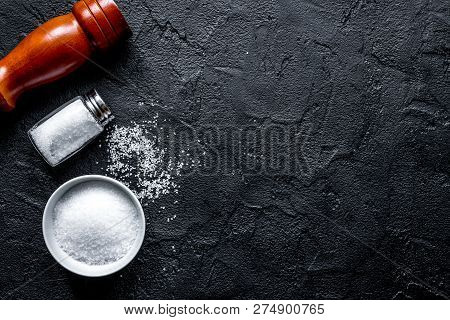Salt In Glass Bottle Scattered On Dark Table Background Top View
