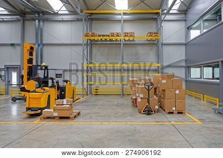 Boxes At Pallet Truck And Electric Forklifts In Distribution Warehouse