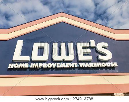 Close-up Logo Of Lowe's Hardware Store Entrance Under Cloud Blue Sky