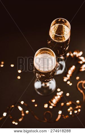 Two Glasses Of Champagne With Decoration On Black Elegant Background. Vertival, Top View. Festive Co