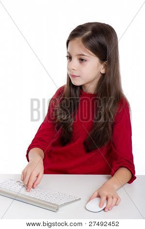 concentrated little girl with Pc keyboard and mouse