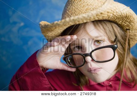Little Girl With Glasses And A Straw Hat
