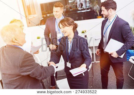Business people shake hands after workshop as thank you sign