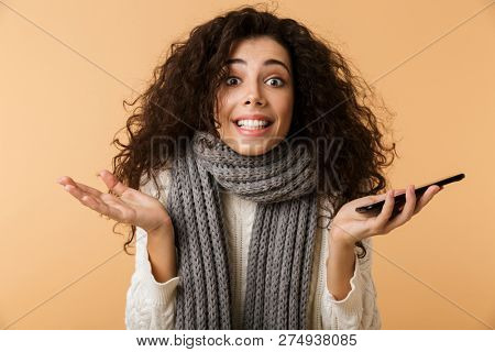 Smiling confused young woman wearing sweater and scarf holding mobile phone isolated over beige background
