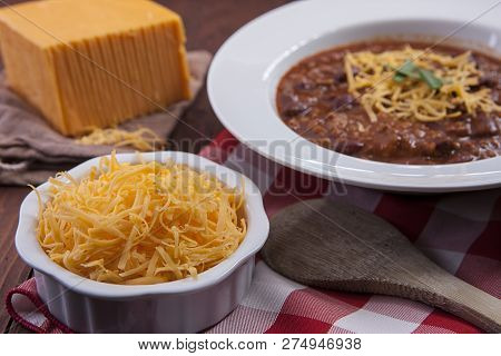 Bowl Of Shredded Cheese And Chili. A Close Up Of A Small Bowl Of Cheddar Heese And A Bowl Of Chili.