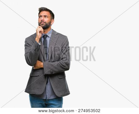 Adult hispanic business man over isolated background with hand on chin thinking about question, pensive expression. Smiling with thoughtful face. Doubt concept.