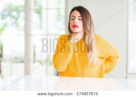 Young beautiful woman wearing winter sweater at home Touching painful neck, sore throat for flu, clod and infection