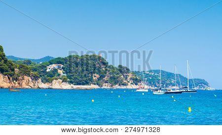 Yachts And Boats Near Coastline Sea In Ibiza. Seascape In Spain. Rocky Coastline In Spanish Mediterr