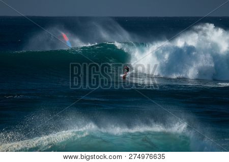 OAHU / USA - 05 DECEMBER 2018: Surfer rides the gigantic wave of Waimea Bay surf spot located on the North Shore of Oahu famous for its surfing opportunities.