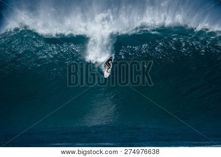 OAHU / USA - 05 DECEMBER 2018: Surfer rides gigantic wave of the Banzai Pipeline surf spot located on the North Shore of Oahu famous for its surfing opportunities.