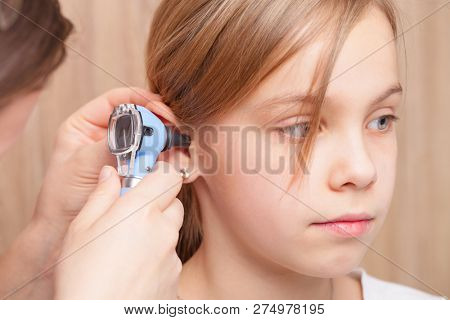 Female pediatrician examines elementary age girl's ear. Doctor using a otoscope or auriscope to check ear canal and eardrum membrane. Child ENT check concept