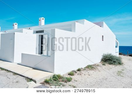 a view of some typical Mediterranean whitewashed houses next to the Mediterranean sea in Amtella de Mar, in the Costa Dorada, Spain
