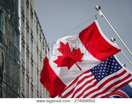 Canadian And Usa Flags In Front Of A Business Building In Toronto Ontario, Canada. Toronto Is The Bi