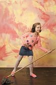Child cleaner with broom on colorful background. Housekeeper kid in earphones. Cleanup and order services. Small girl listen music with mop. Cleaning and purity. poster
