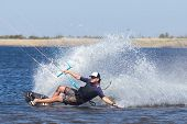 Kitesurfing. The young man is flying on the sea wave on the Board. poster